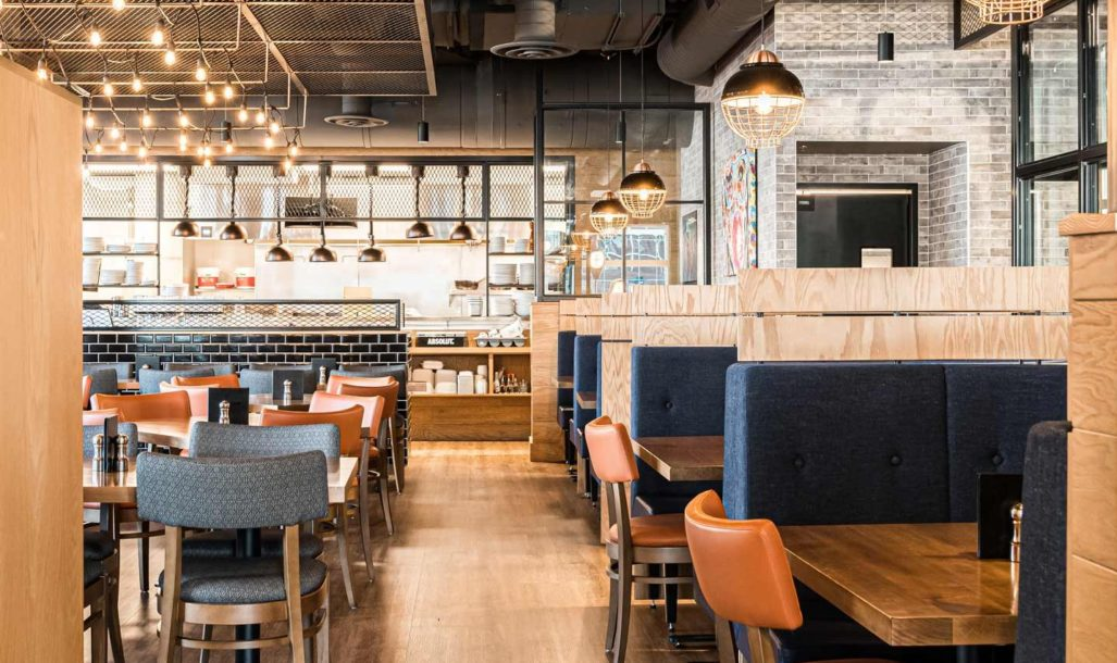 Restaurant dining room with modern blue and orange seating and industrial style hanging lighting